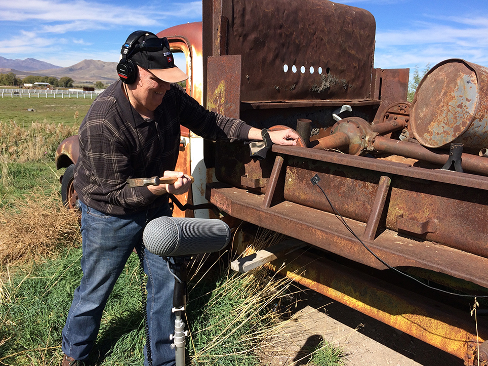 Mike hitting an old truck with a hammer for metal bangs.