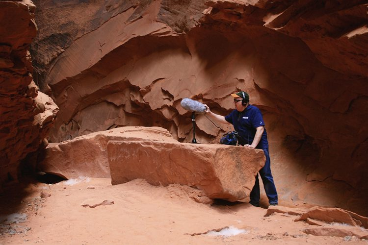 Mike McDonough field recording rocks in southern Utah slot canyon